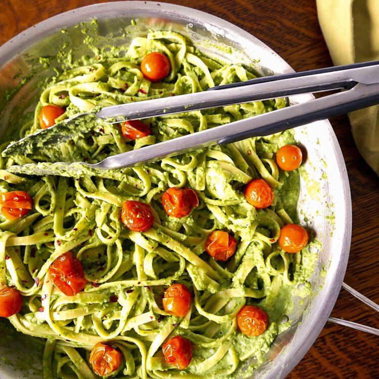 vegan pea pesto pasta in skillet with tongs