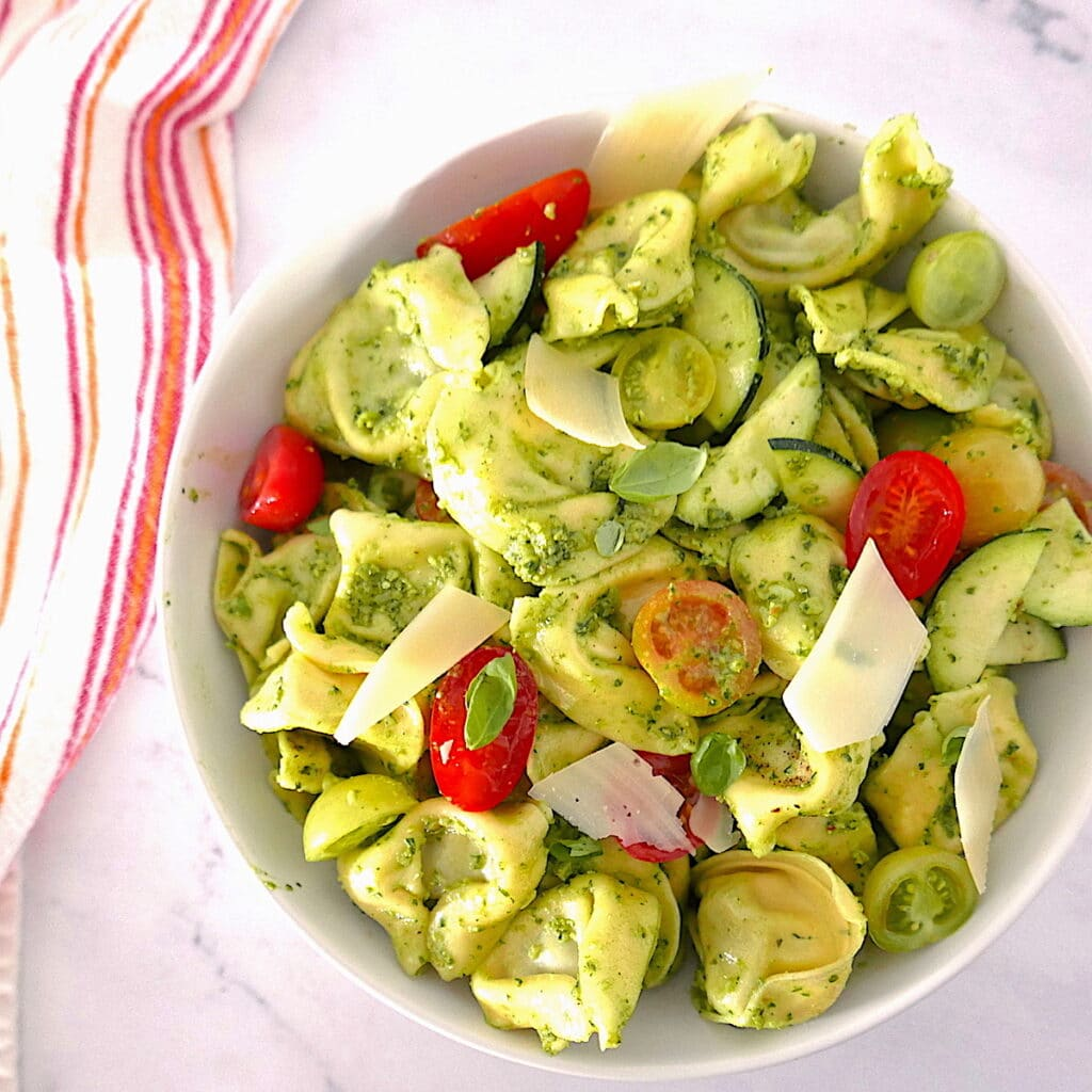 summer tortellini salad in a white bowl with red dish cloth next to bowl