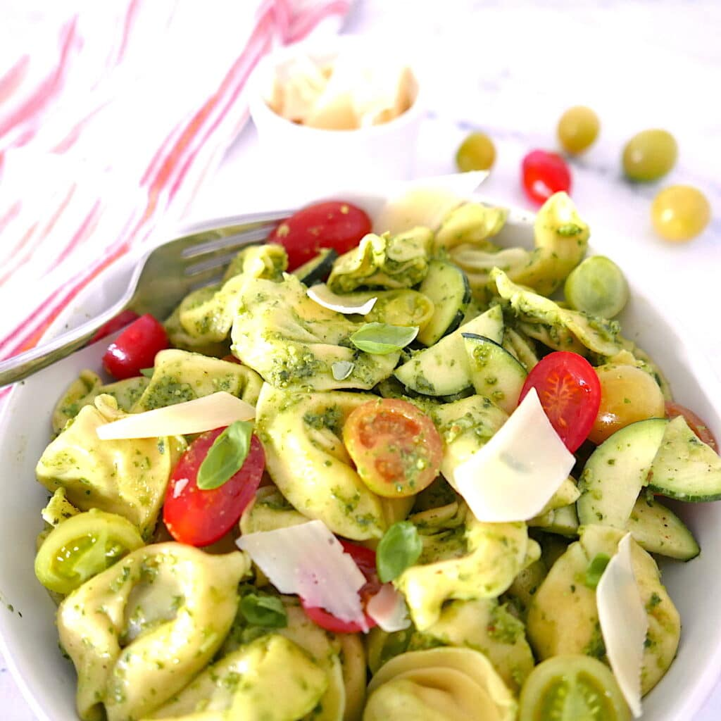 white bowl with pasta salad with cherry tomatoes in background
