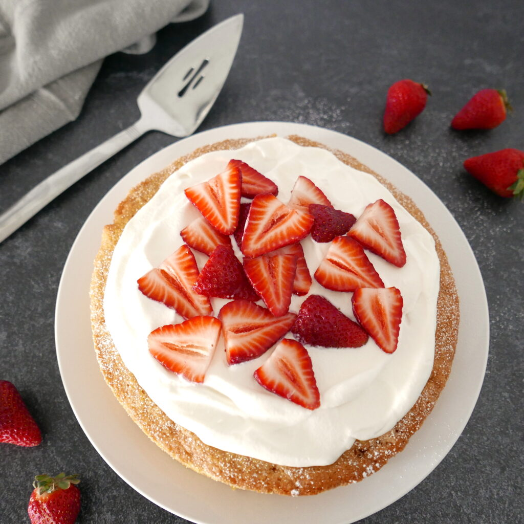 strawberry cornmeal cake with whipped cream on a white platter with strawberries and a pie server in the background
