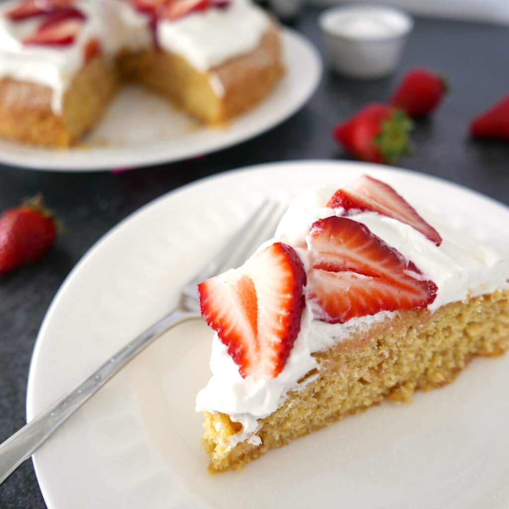 strawberry cornmeal cake with whipped cream on a white platter with one piece of cake on a white plate in the foreground