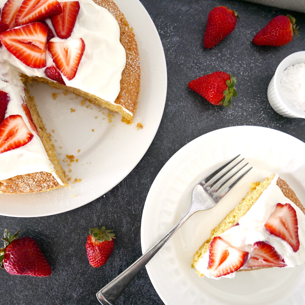 overhead view of strawberry cornmeal cake on a white platter with one piece on a plate next to it