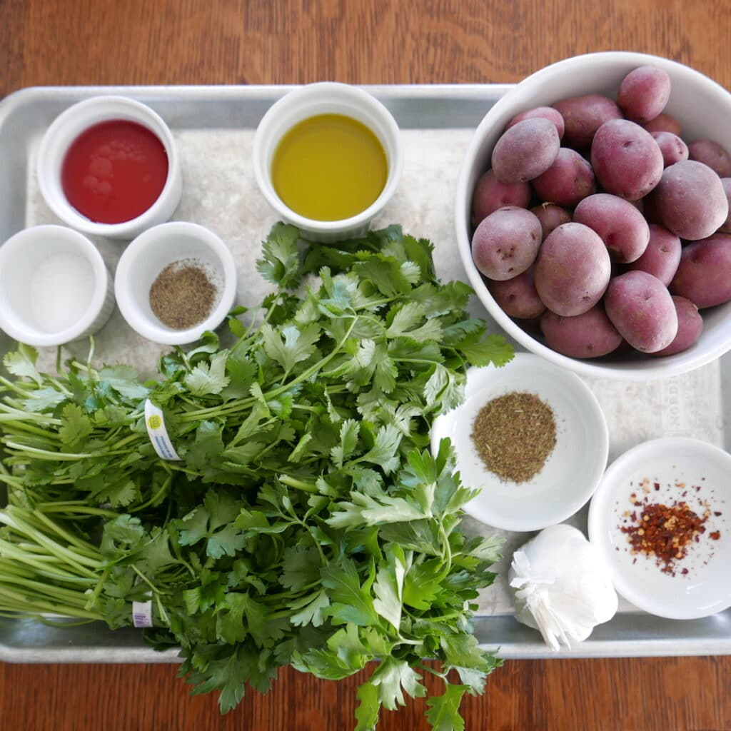 ingredients for roasted red skin potatoes with chimichurri on a baking sheet