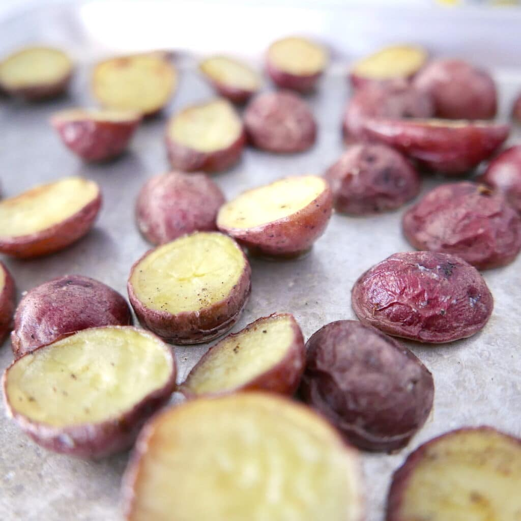 roasted red potatoes cut in half spread out on a baking sheet