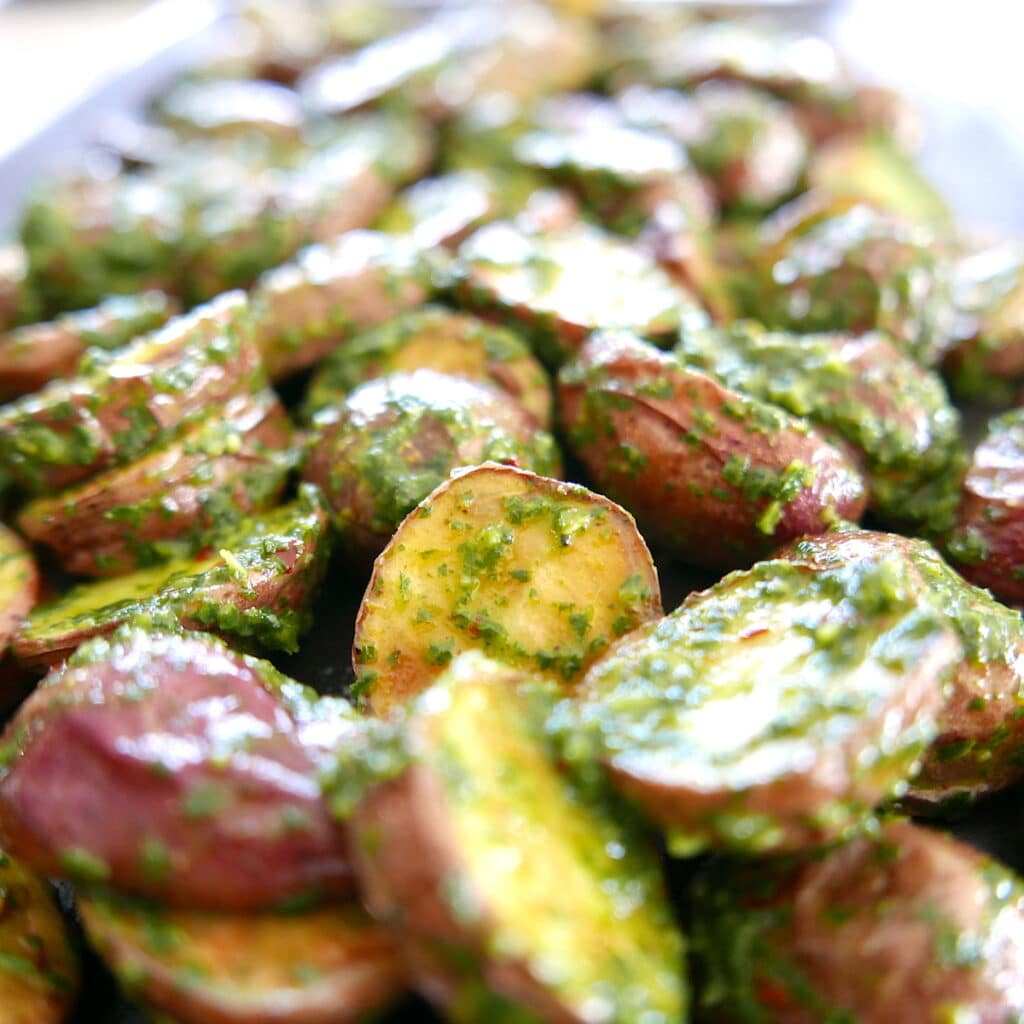 baked redskin potatoes with chimichurri on a baking sheet