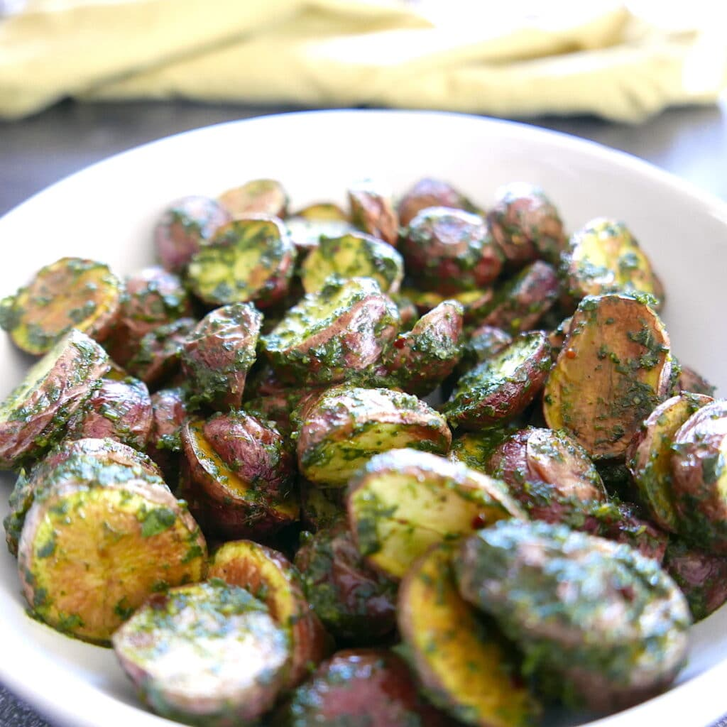 baked redskin potatoes with chimichurri in a white bowl with a green napkin in background