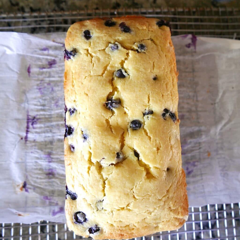 loaf of blueberry lemon pound cake resting on cooling rack