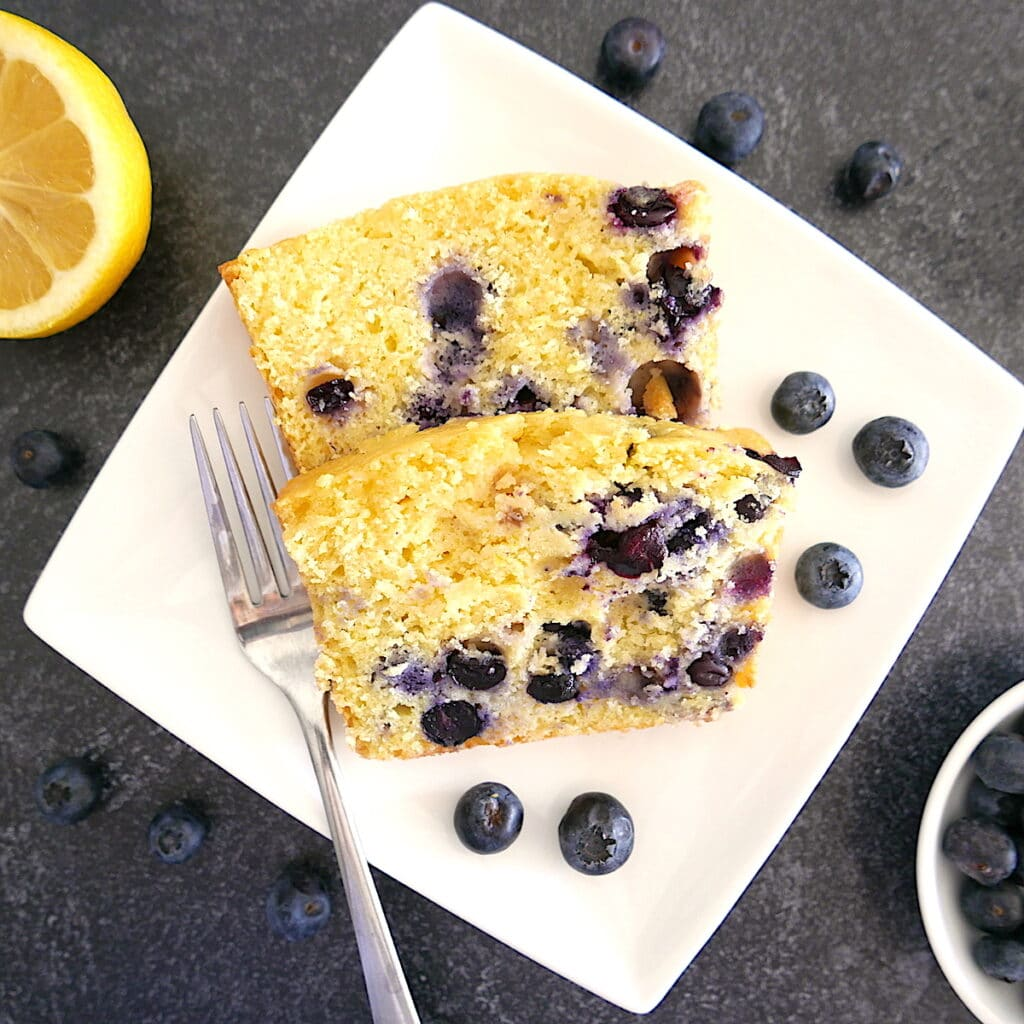 two slices of blueberry lemon ricotta pound cake laying on a white plate with fresh blueberries and a fork on the  plate