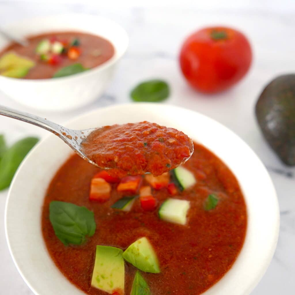 silver spoon holding up a spoonful of gazpacho over a white bowl