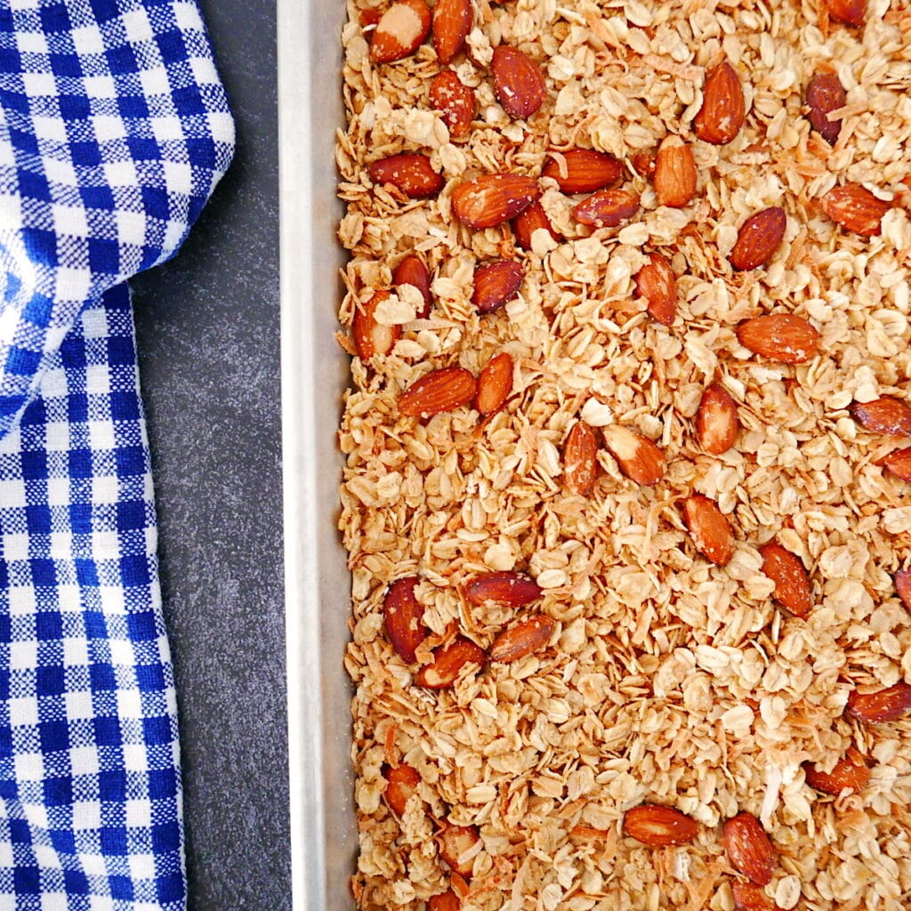 pan of coconut almond granola on a baking sheet with a checkered dish towel next to it