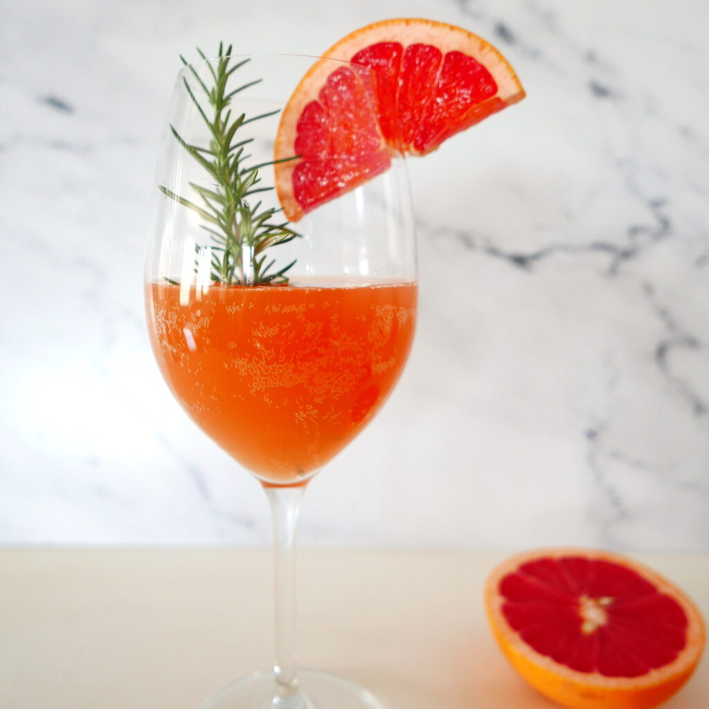 pink grapefruit vodka cocktail in a wine glass with slice of grapefruit stuck on side of glass