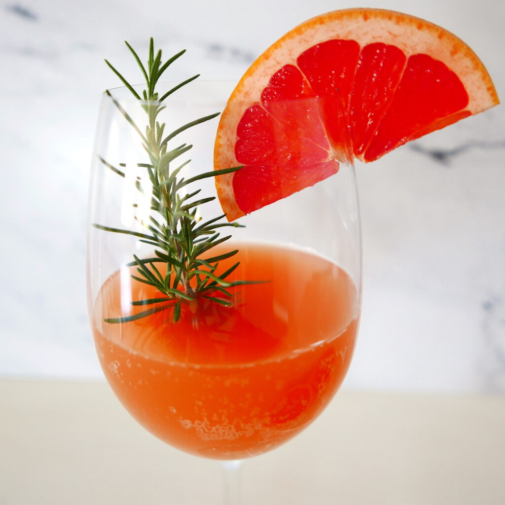 vodka grapefruit cocktail with rosemary sprigs in a large wine glass