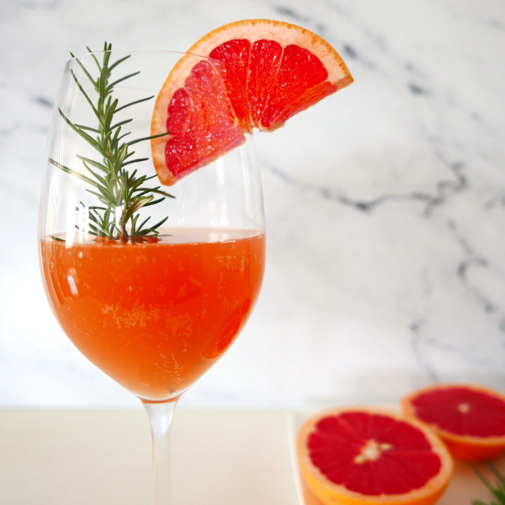 pink grapefruit cocktail in wine glass with cut grapefruit in background