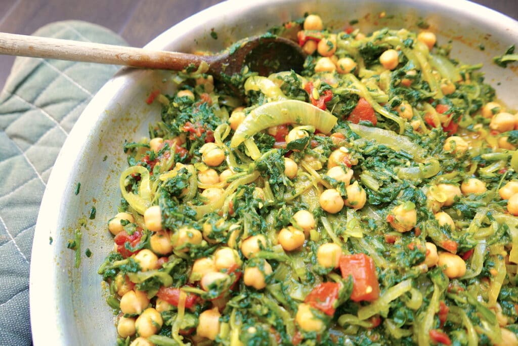 chickpea saag in a silver skillet with wooden spoon