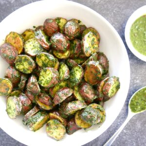 roasted red potatoes with chimichurri in a white bowl