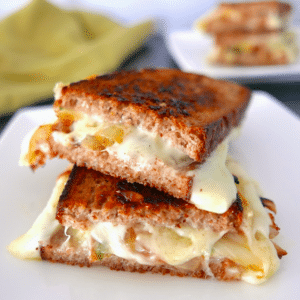 french onion grilled cheese cut in half and arranged on a white plate