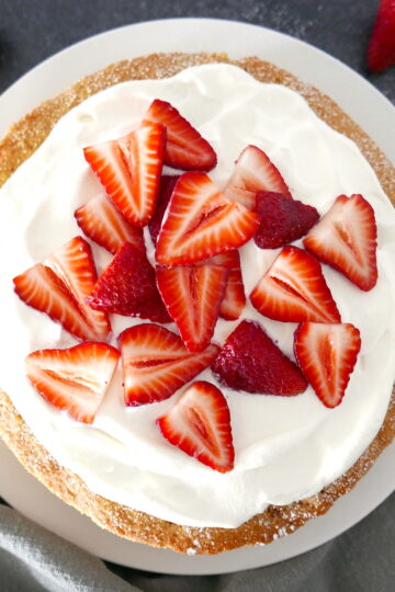 strawberry cornmeal cake with whipped cream and strawberries on a white platter with a grey napkin