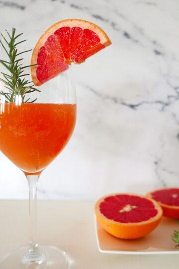 pink grapefuit vodka cocktail with grapefuit halves in background