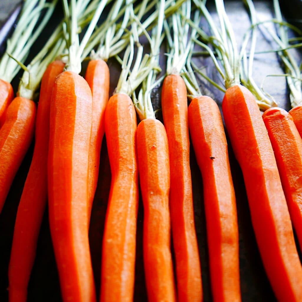 peeled carrots arranged on a baking sheet