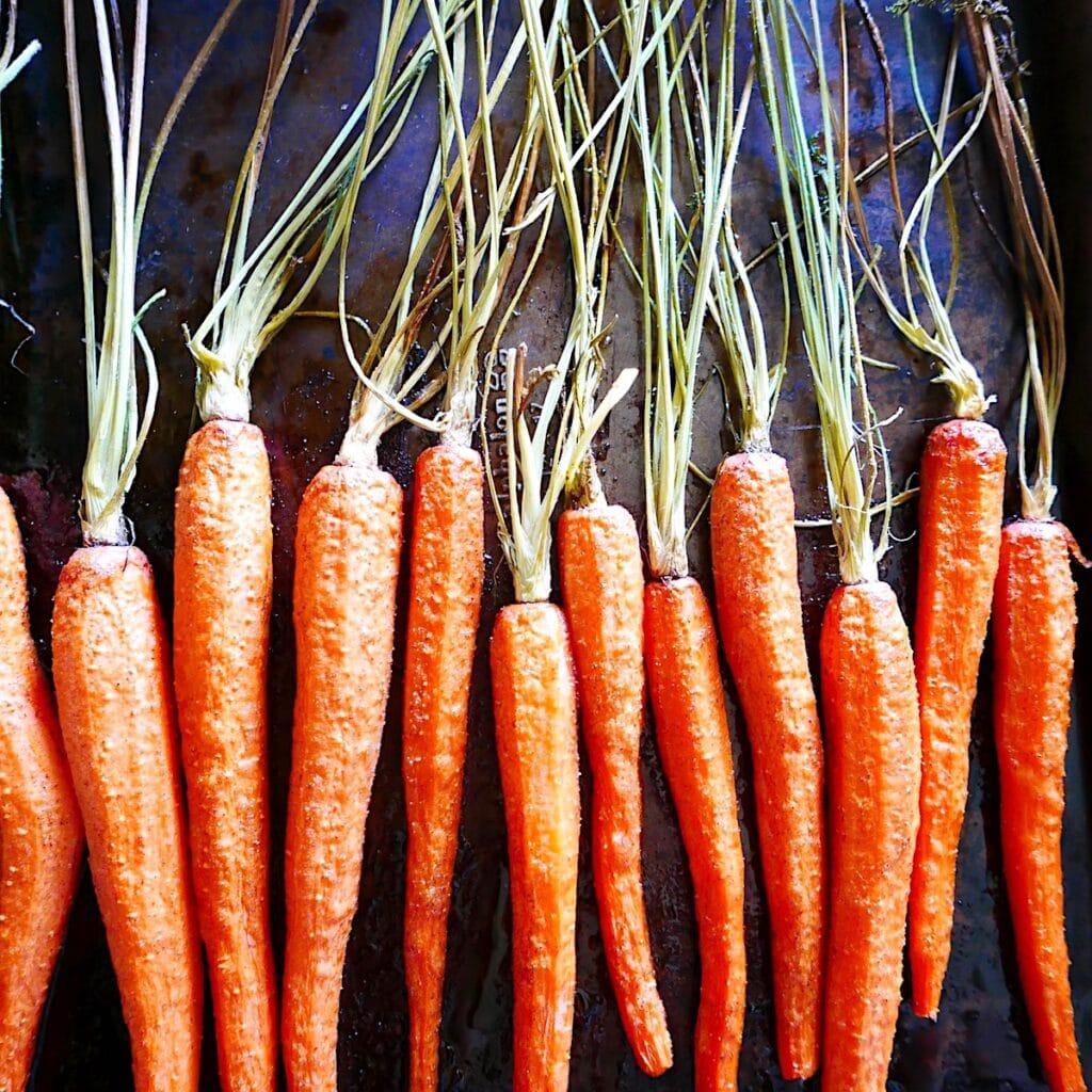roasted carrots arranged on a baking sheet