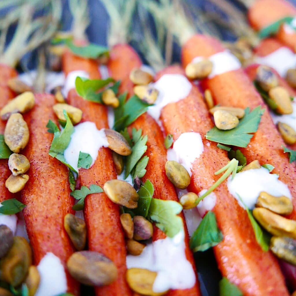 close up of cumin roasted carrots with yogurt sauce and pistachios sprinkled on top