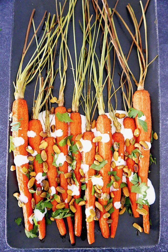 cumin roasted carrots with yogurt sauce, pistachios, and parsley arranged on a grey platter