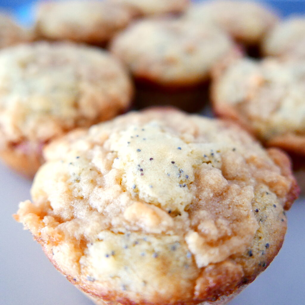 close up of almond poppy seed muffins arranged on a white platter