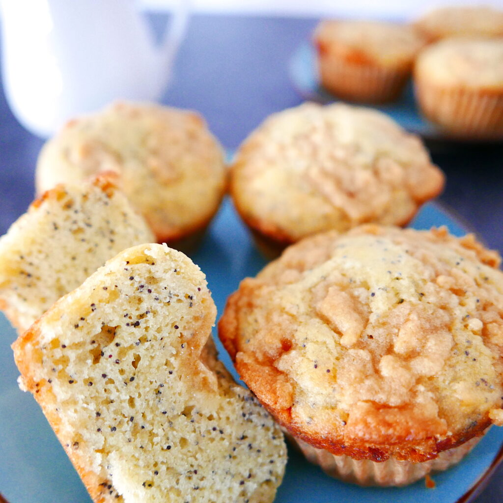 almond streusel muffins arranged on a blue plate with one cut in half