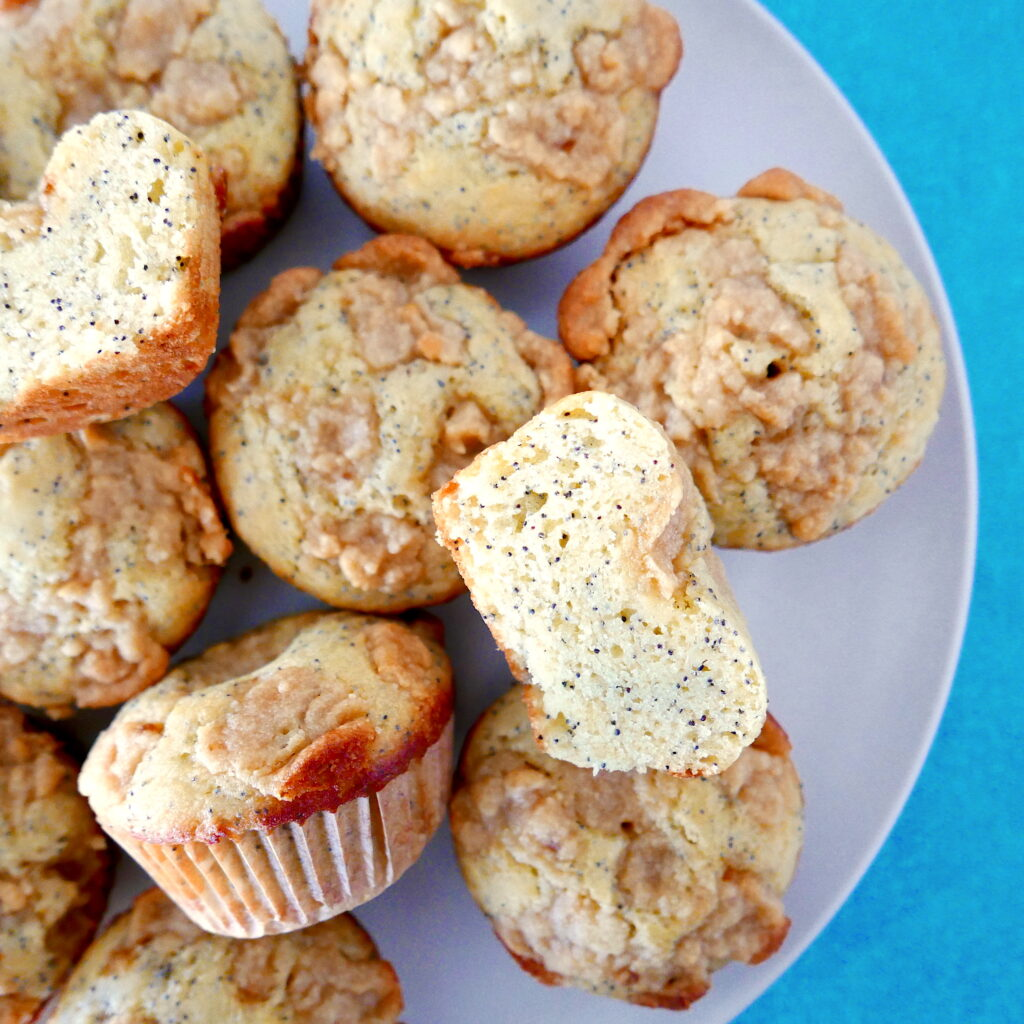 almond poppy seed muffins with almond paste streusel arranged on a white platter with one muffin cut in half