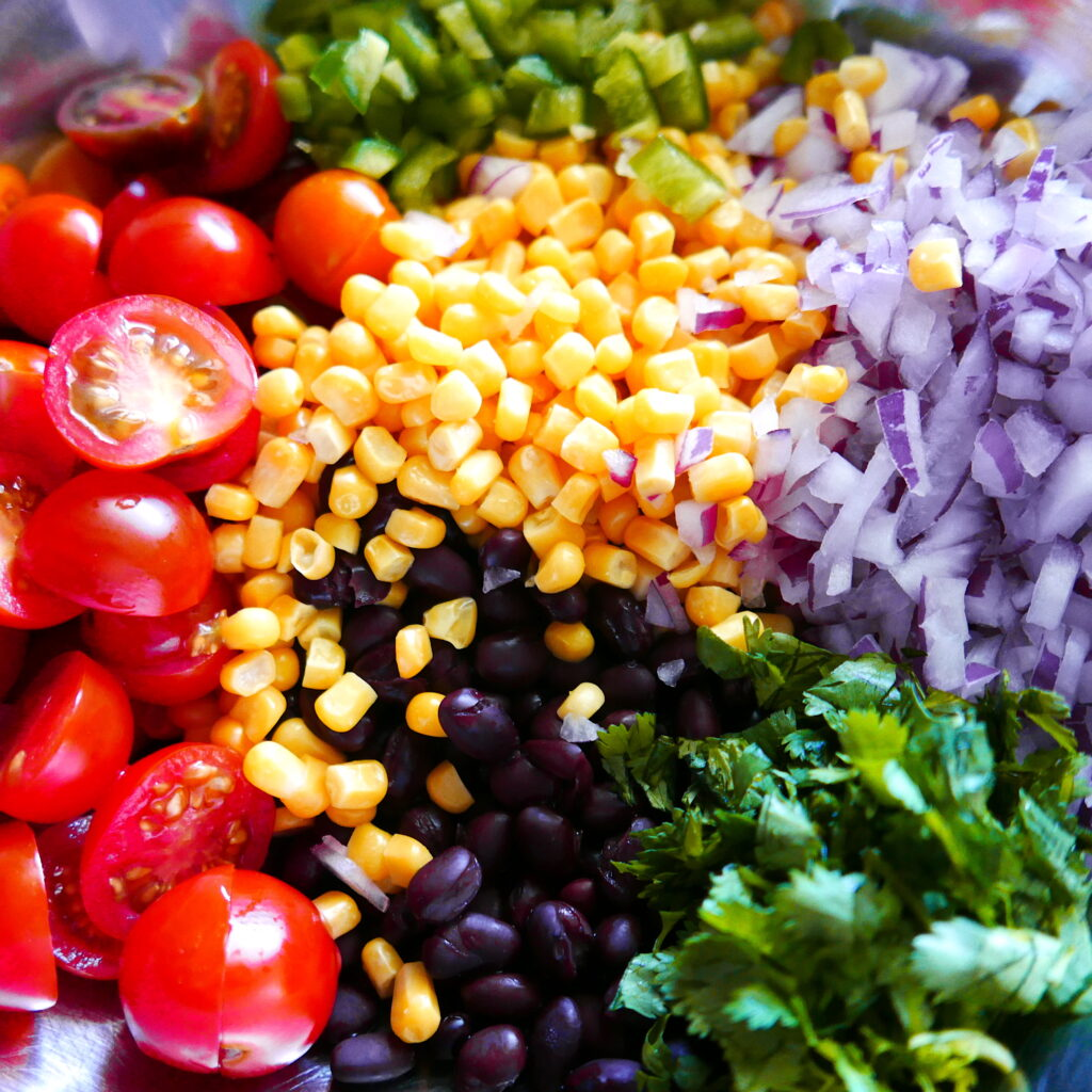 cherry tomatoes, corn, diced jalapeno, diced red onion, black beans, and cilantro in a silver mixing bowl