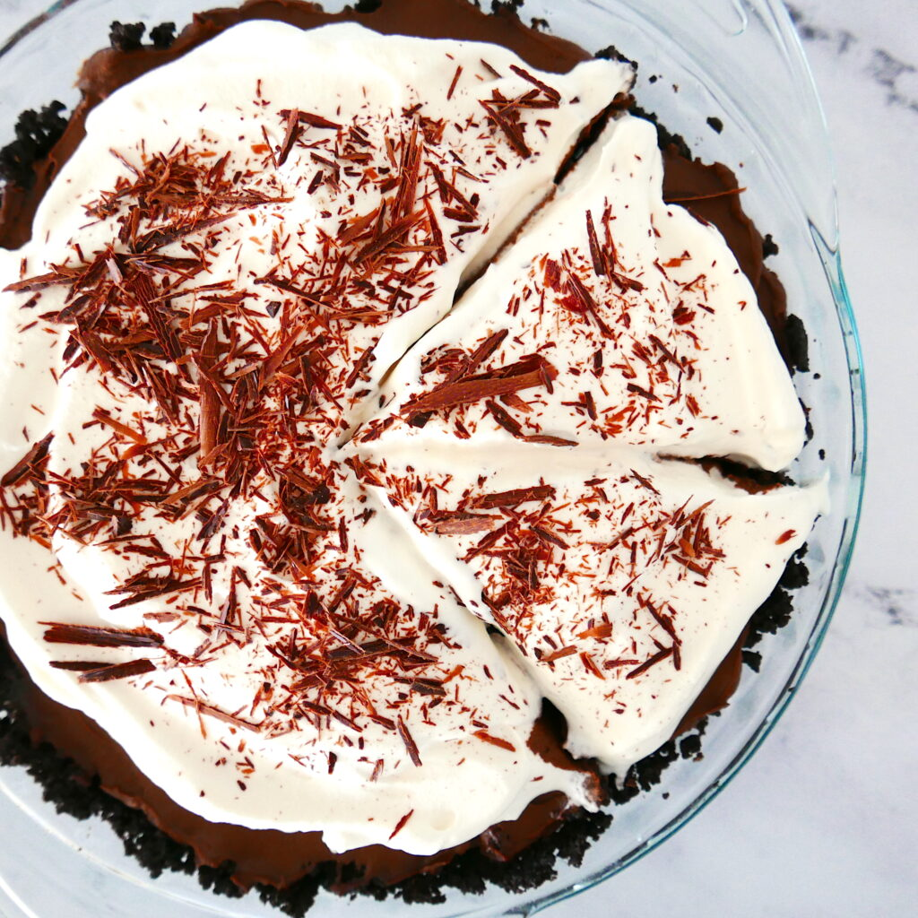chocolate cream pie with oreo crust in a pie shell with two pieces cut