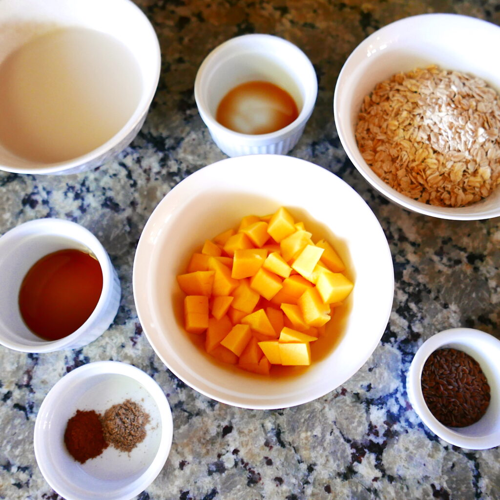 white bowls arranged on a counter with oats, diced mango, maple syrup, almond milk, and cinnamon