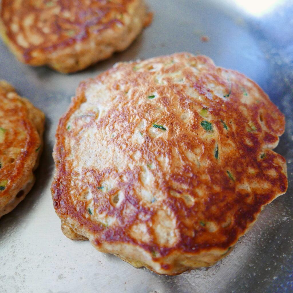three zucchini bread pancakes in a skillet