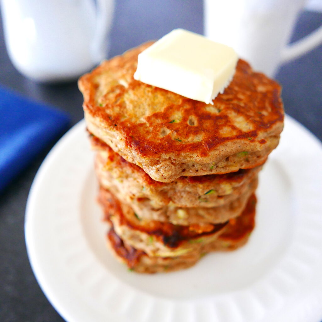 a large stack of zucchini pancakes with a square of butter on top arranged on a white plate with white coffee cup in background and blue napkin next to it