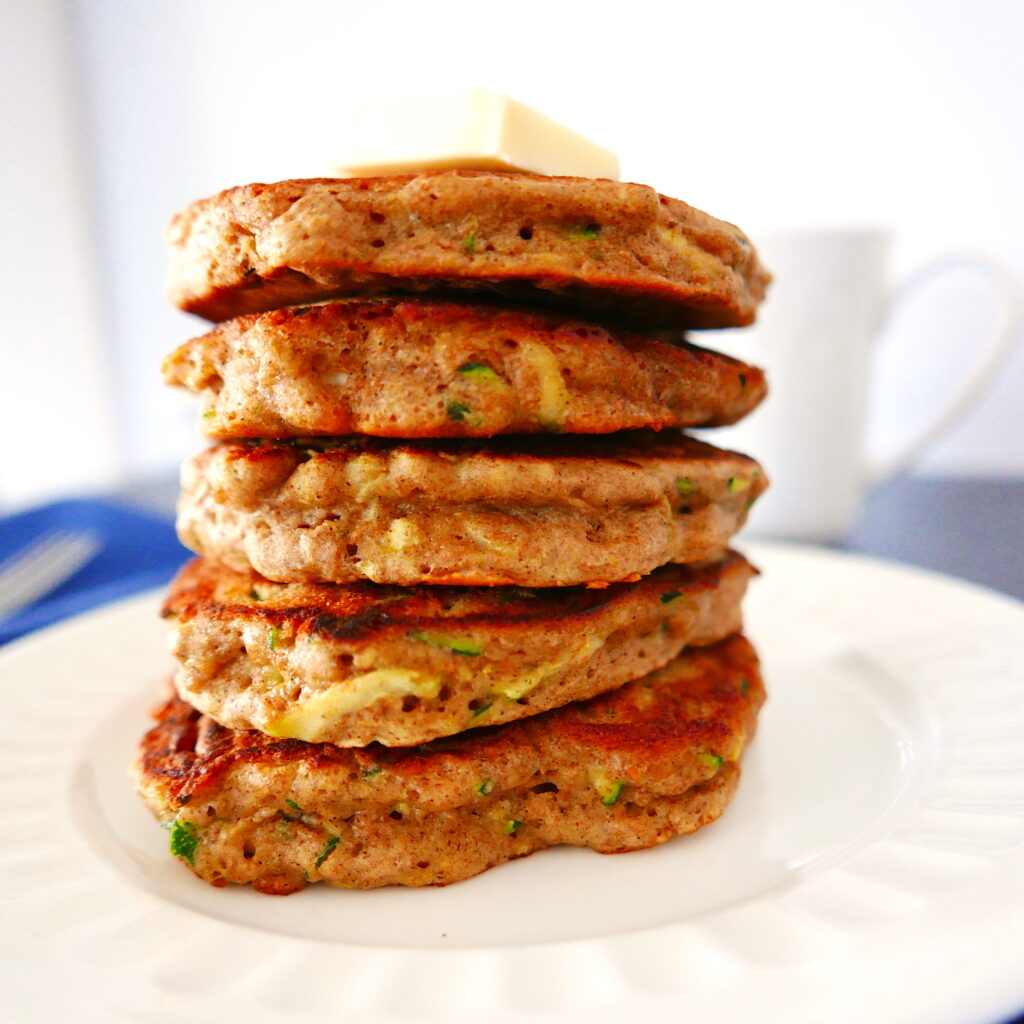 five zucchini bread pancakes stacked on a white plate with a white coffee cup in background
