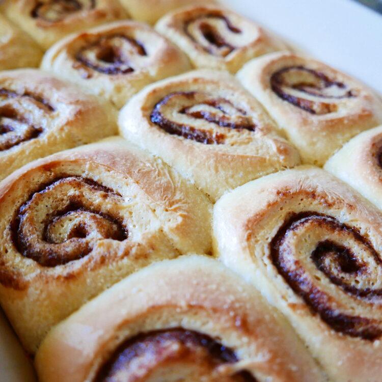 gooey cinnamon buns in a white baking dish