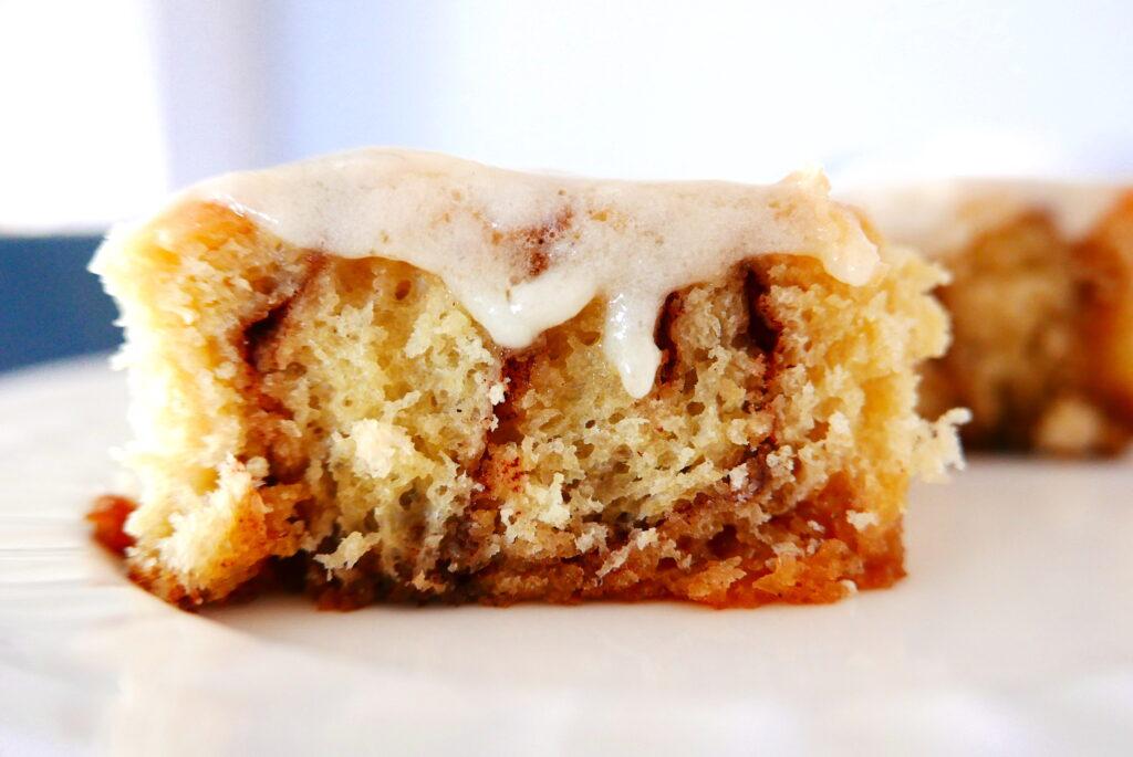 gooey cinnamon bun recipe with cream cheese cut in half resting on a white plate