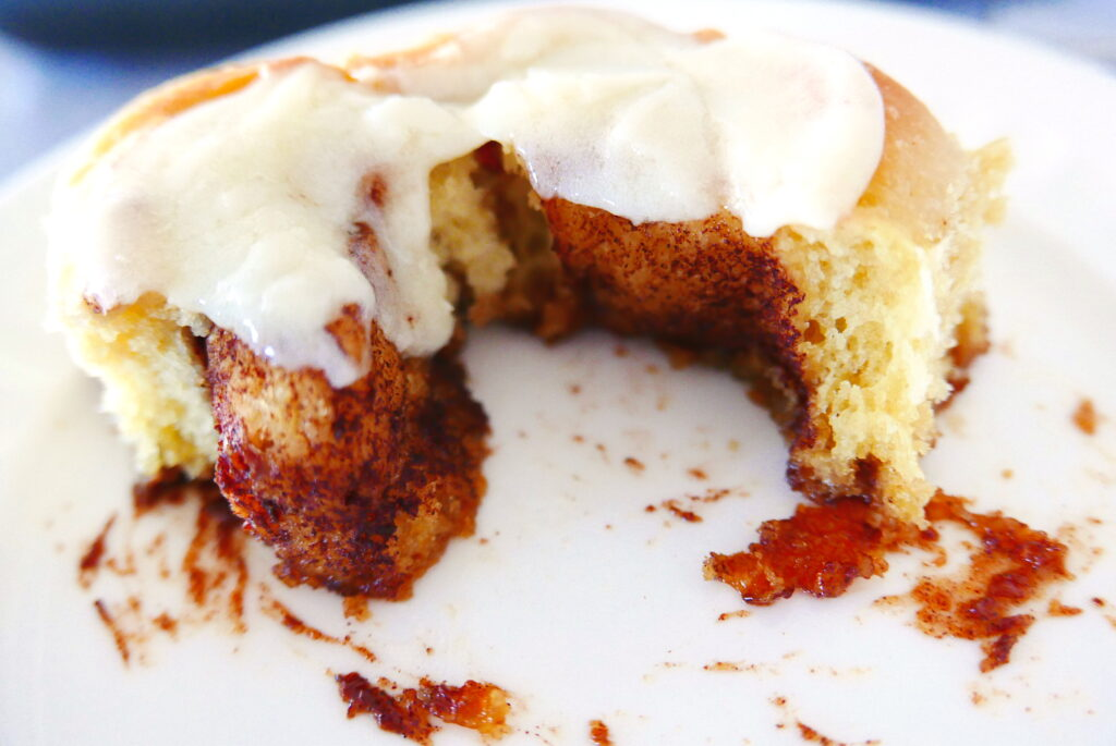 sticky and gooey cinnamon bun with cream cheese cut open and sitting on a white plate