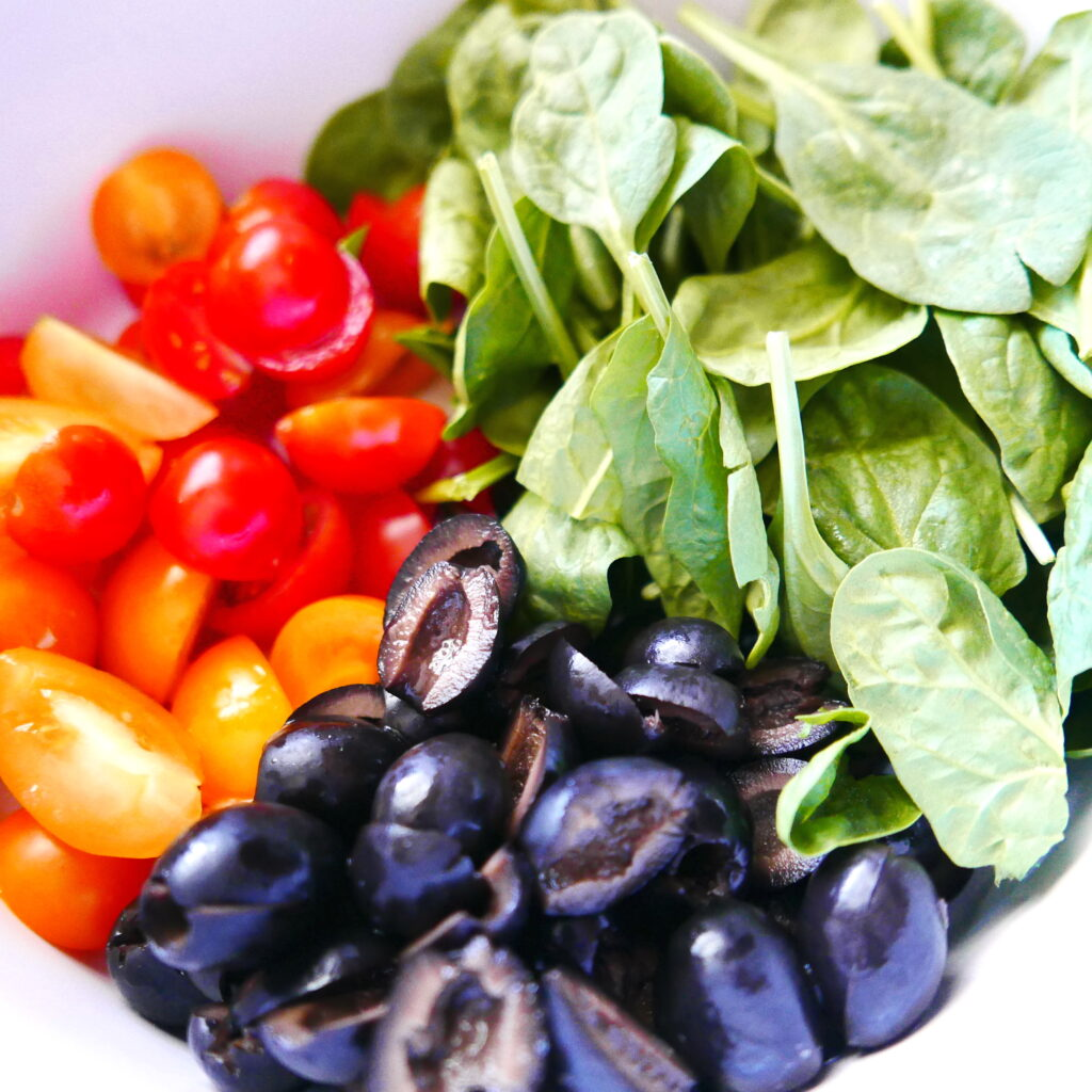 mixing bowl with spinach, black olives, and cherry tomatoes