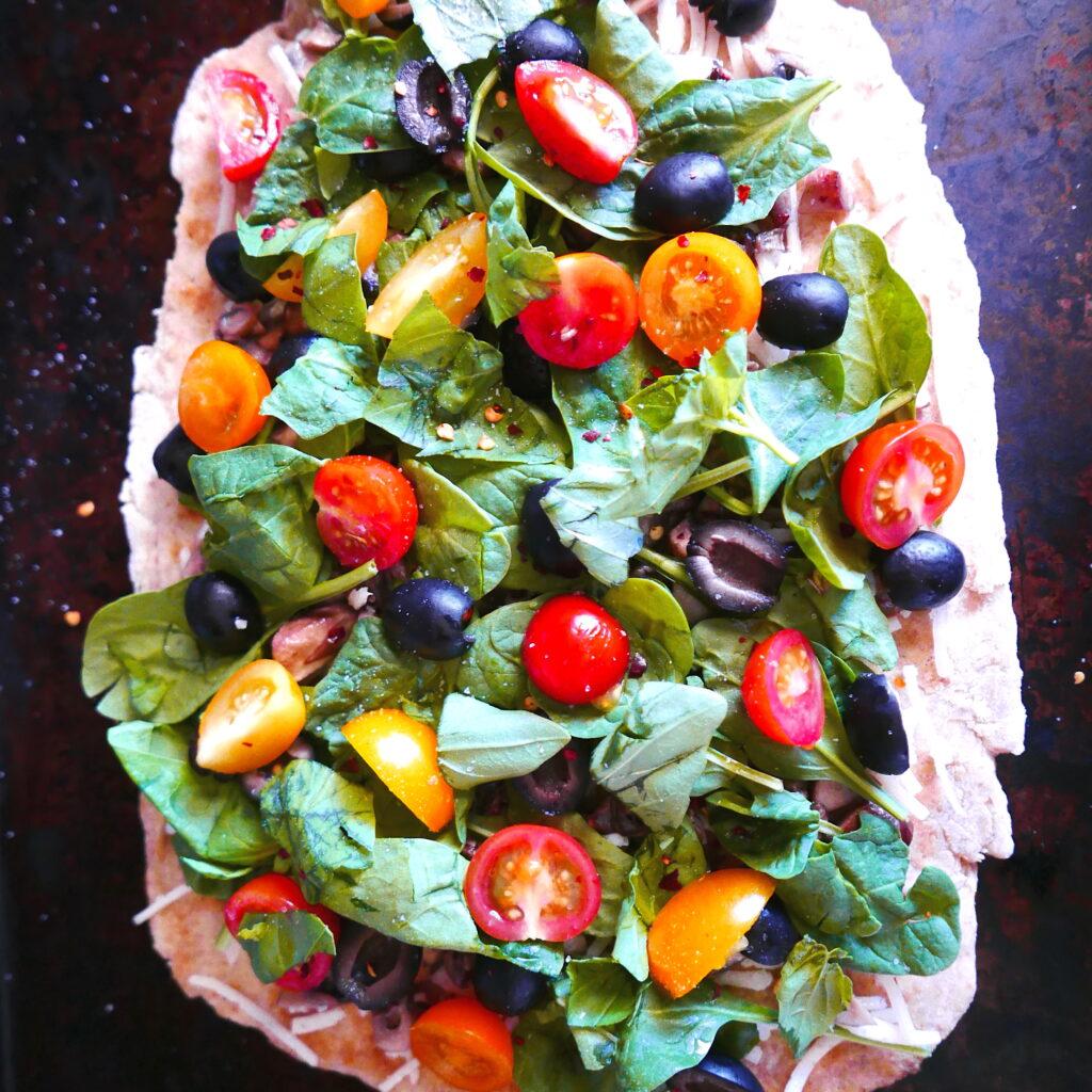 veggie lovers flatbread pizza resting on a baking sheet