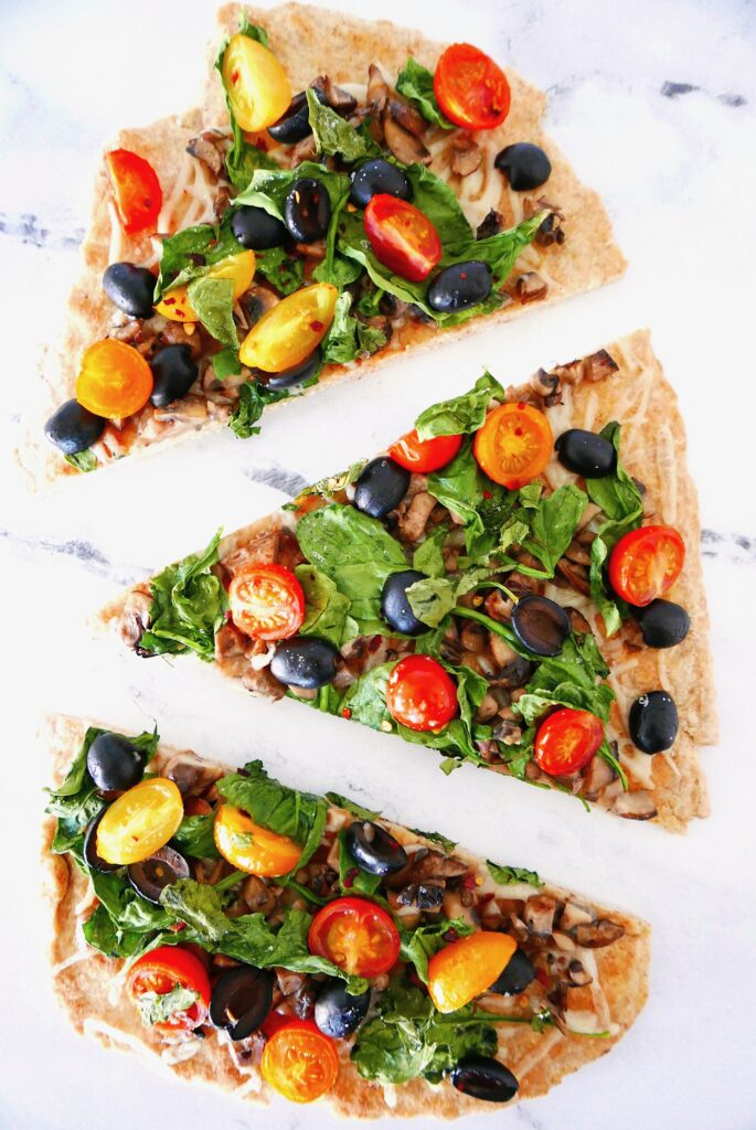 vegan flatbread pizza with lots of veggies cut into 3 slices and sitting on a marble counter