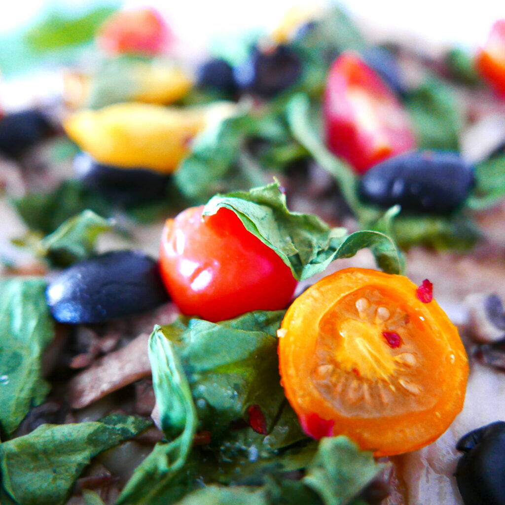 close up of cherry tomatoes, black olives, and spinach on a vegan flatbread pizza