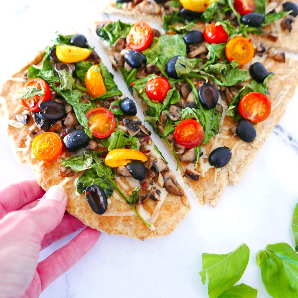 white hand picking up a piece of vegan flatbread pizza with lots of vegetables on top