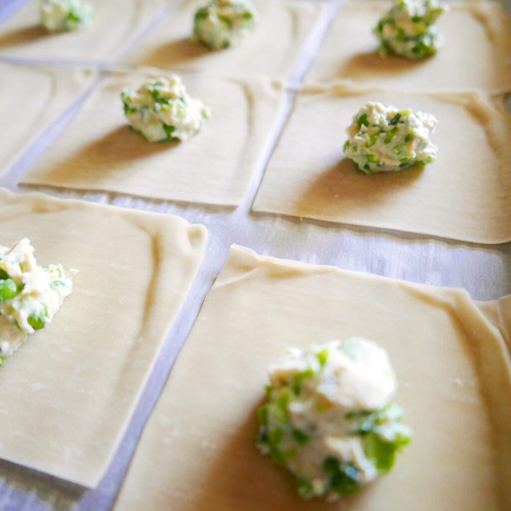 vegetarian pea ricotta ravioli being assembled on a baking sheet