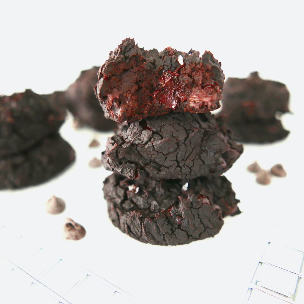 black bean cookies stacked three high with more cookies in the background and chocolate chips scattered around