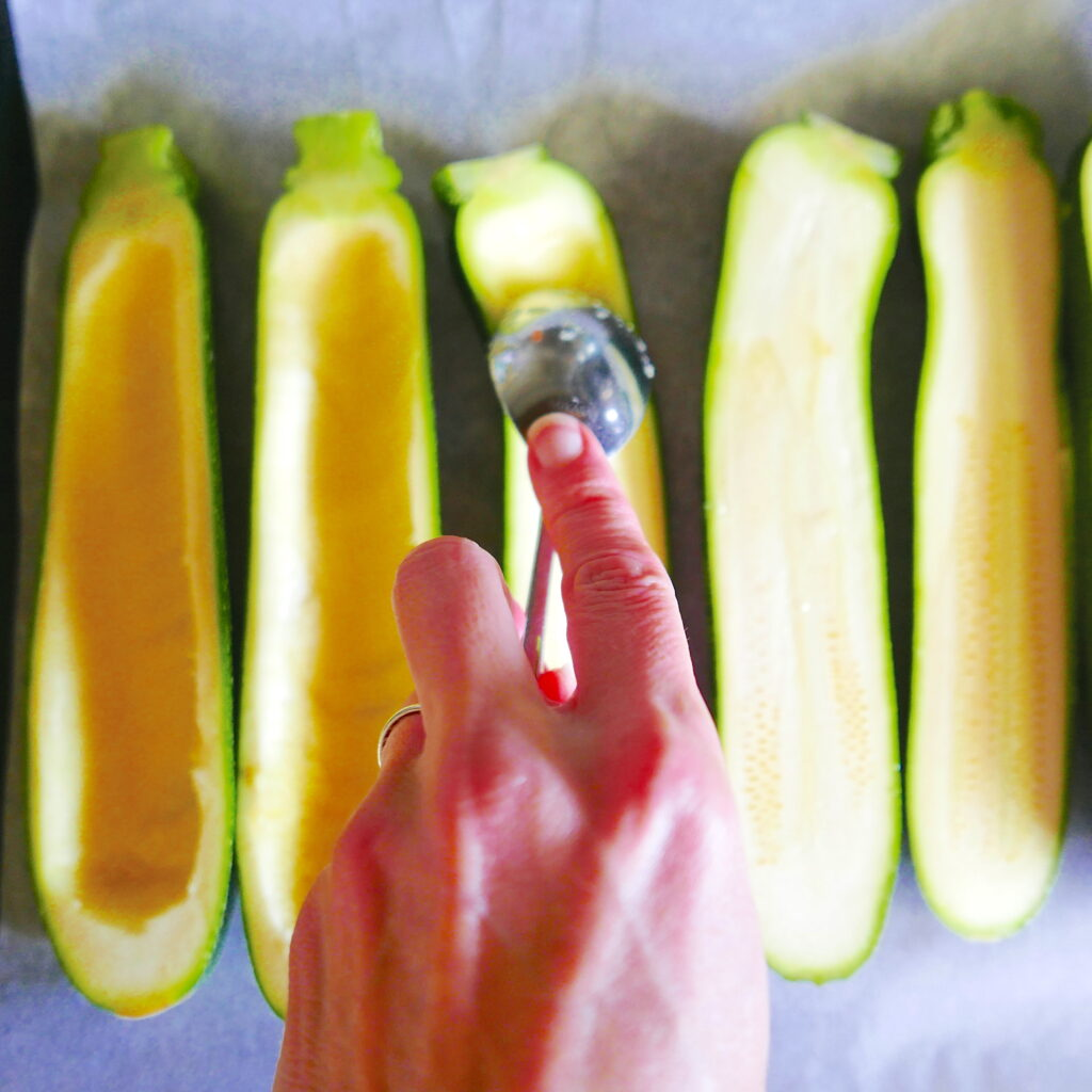 white hand holding a spoon hollowing out zucchinis that are lined up on a baking sheet