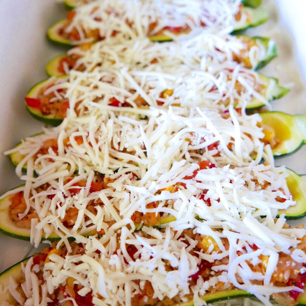 mozzarella, rice, tomato, and onion topped zucchini  arranged on a white platter