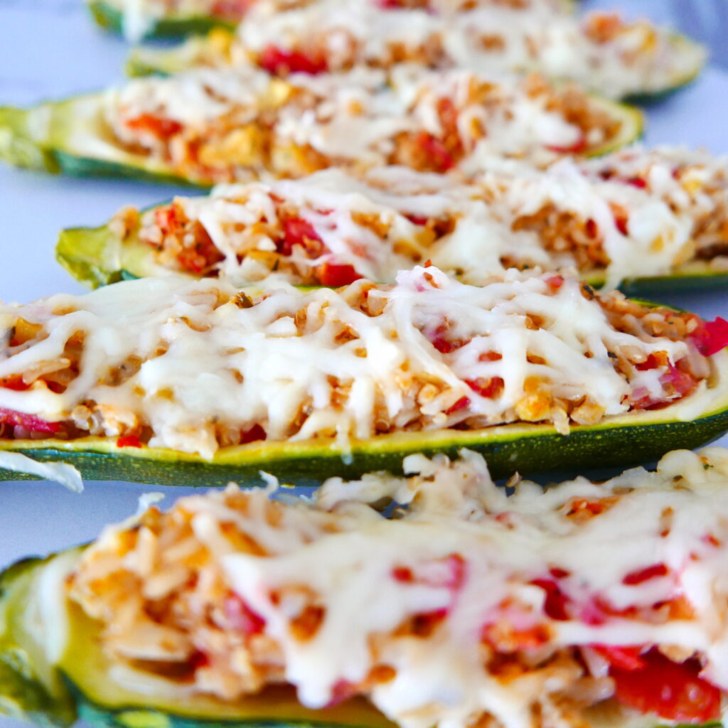 close up of four stuffed zucchini with melted mozzarella on top