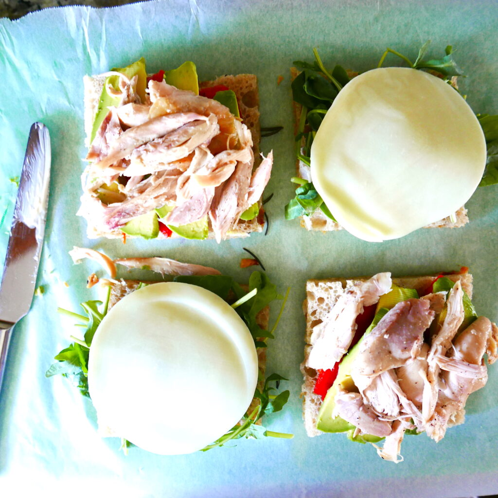 two chicken avocado focaccia sandwiches being assembled on a green cutting board