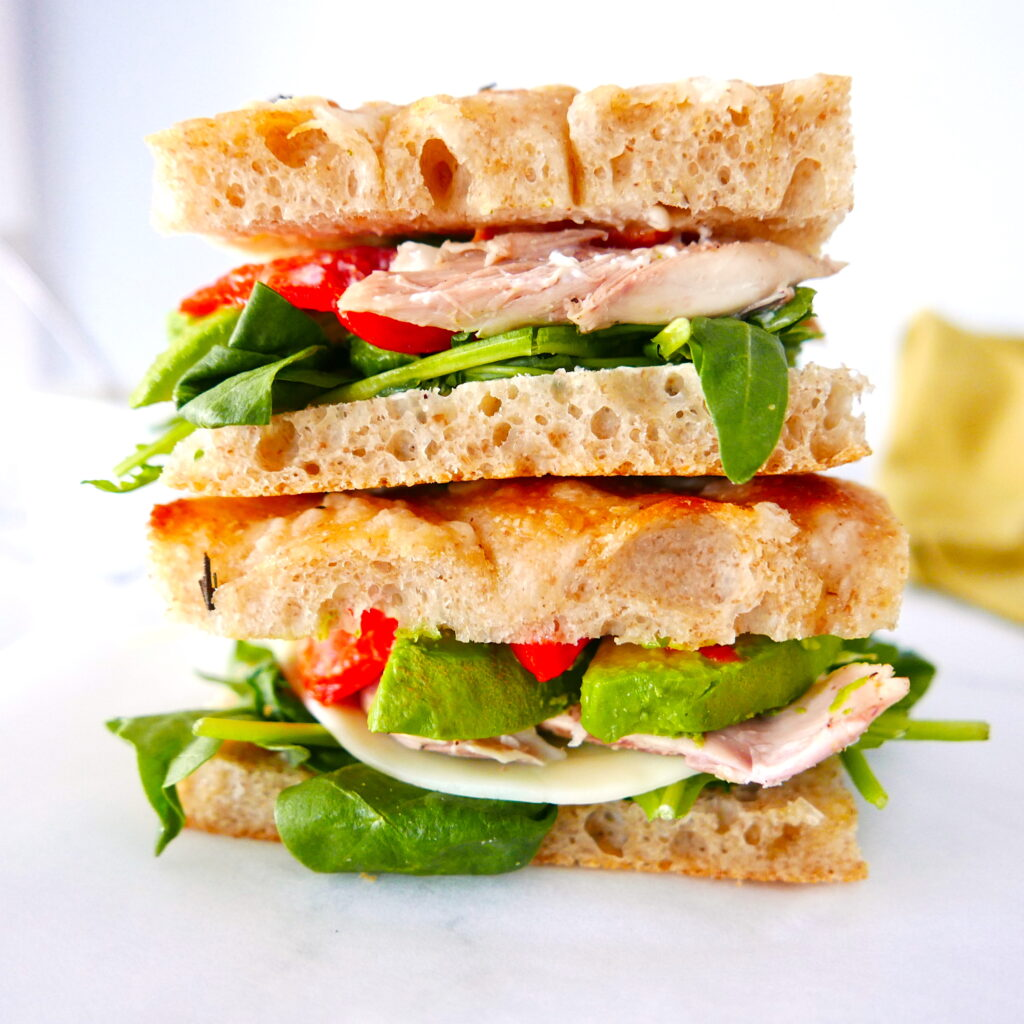 two chicken focaccia sandwiches with roasted red pepper stacked on top of each other
